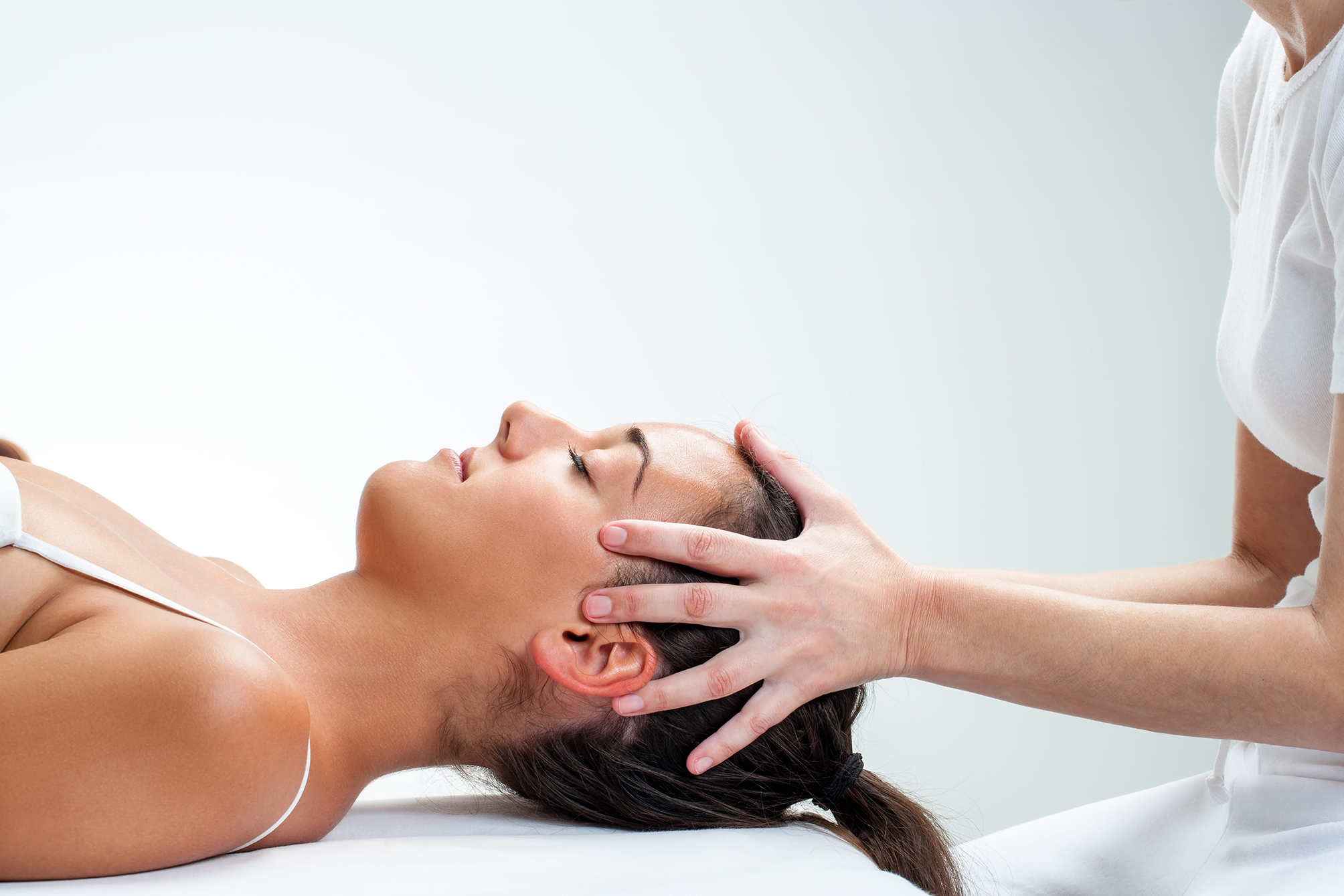 A woman receiving a head massage